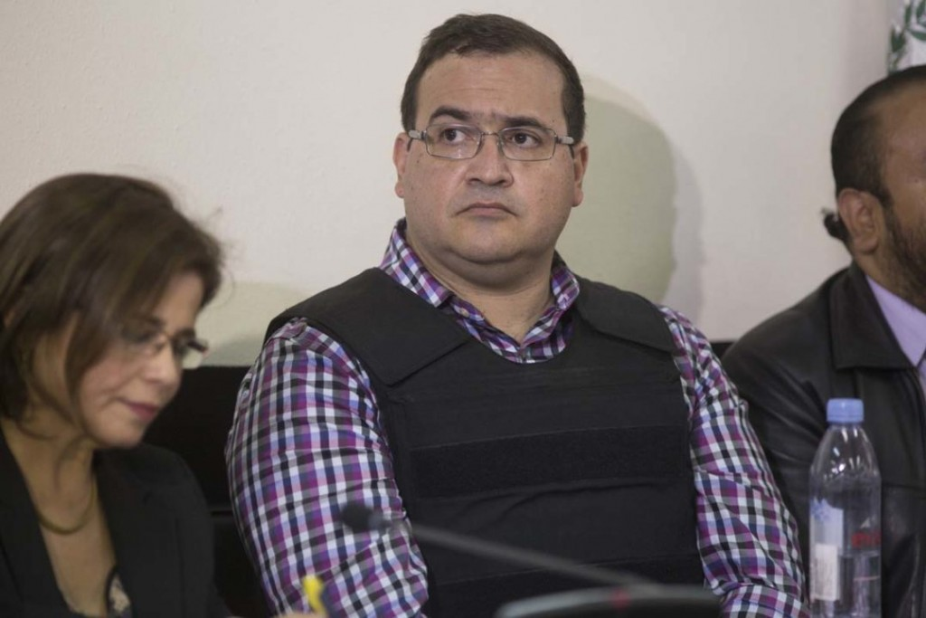 Mexico's former Veracruz state Gov. Javier Duarte, center, accompanied by his lawyers waits for an extradition hearing in Guatemala City, Wednesday, April 19, 2017. Duarte was detained Saturday in Guatemala after six months as a fugitive and high-profile symbol of government corruption in his country. (AP Photo/Luis Soto)